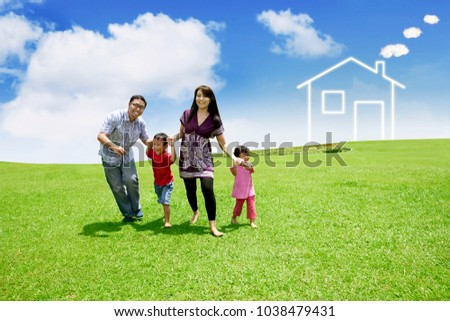 Happy family playing together while running in the meadow with house symbol background
