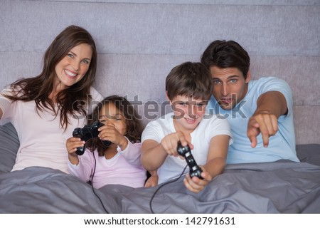 Happy family playing video games on bed