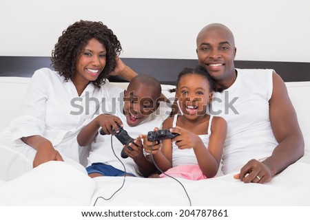 Happy family playing video games together in bed at home in the bedroom - stock photo