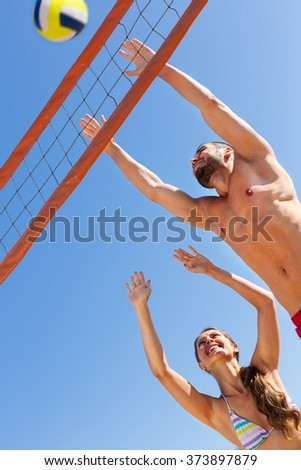 Happy family playing volleyball and having fun on a shore  - stock photo