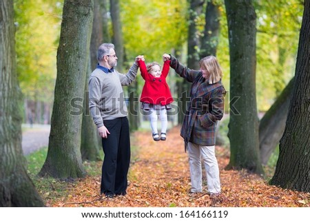 Happy family playing with a little toddler girl in an autumn park with beautiful yellow trees - stock photo