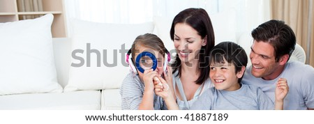 Happy family playing with a magnifying glass in the living-room - stock photo