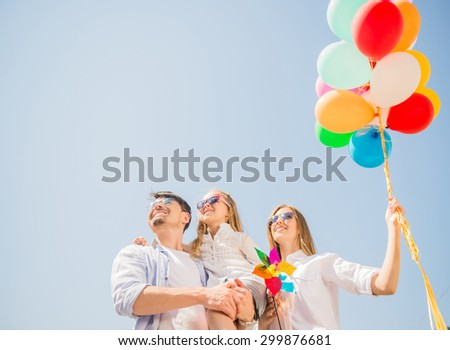 Happy family playing with balloons at the day time. Friendly family concept. Sky background. - stock photo