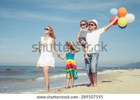 Happy family playing  with balloons on the beach at the day time. Concept of friendly family. - stock photo