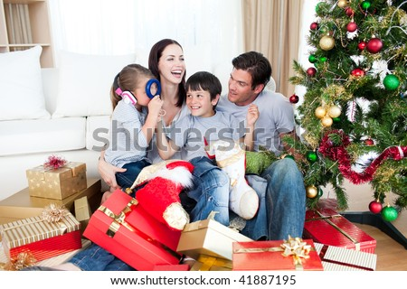 Happy family playing with Christmas gifts at home - stock photo