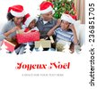 Happy family playing with Christmas presents against joyeux noel - stock photo