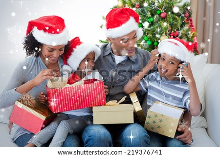 Happy family playing with Christmas presents against snow falling - stock photo