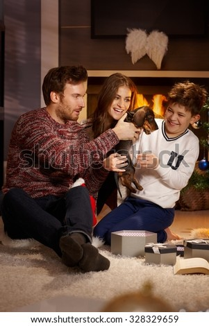 Happy family playing with dachshund puppy received for christmas. - stock photo