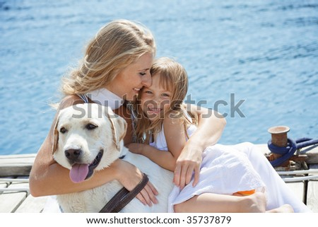 Happy family playing with dog on berth near sea in summer - stock photo