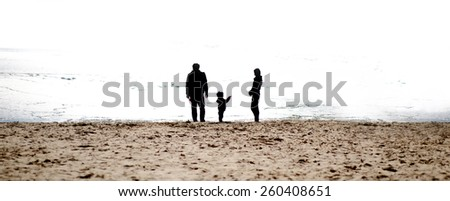 Happy family playing with her child on the beach. Family silhouettes on the beach in The morning. Copy space. . Extreme Wide Shot.  - stock photo