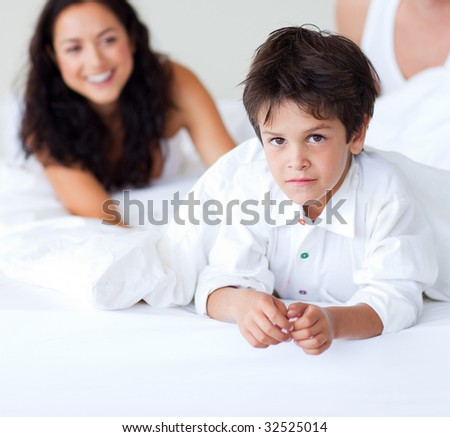 Happy family playing with his son in bed - stock photo