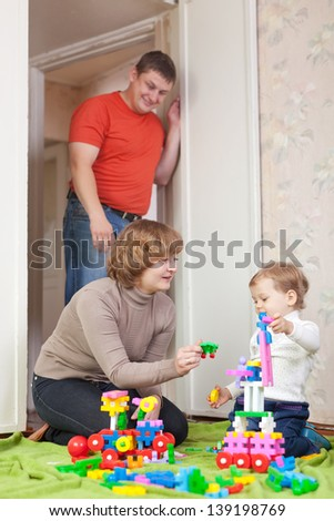 Happy family plays in home interior - stock photo