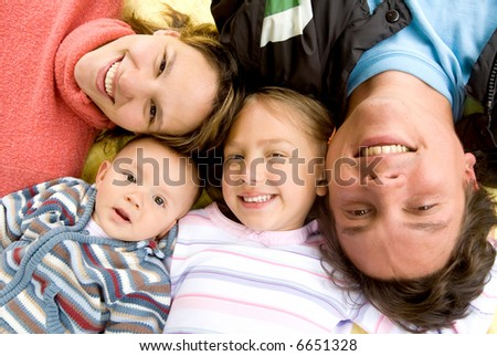 happy family portrait all smiling on the floor with heads together - stock photo