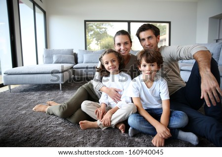 Happy family portrait at home sitting on carpet - stock photo