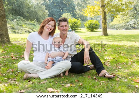 Happy Family Portrait at Park. They are three persons, all wearing white shirts and sitting on the grass, embraced together and looking at camera. - stock photo