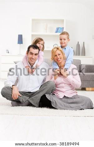 Happy family portrait, children hugging their parents. - stock photo