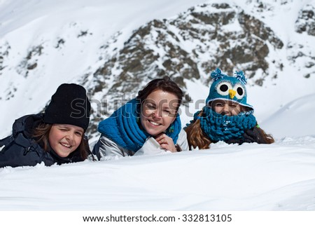 Happy family portrait in the snowy mountains on a bright sunny day - stock photo