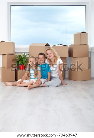 Happy family portrait in their new home sitting with cardboard boxes in front of window - stock photo