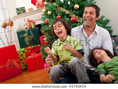 Happy family portrait laughing next to a Christmas tree - stock photo
