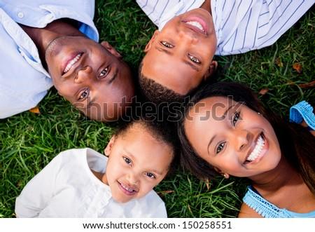 Happy family portrait lying on the floor outdoors  - stock photo