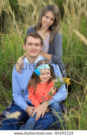 Happy family portrait of a young family outdoors