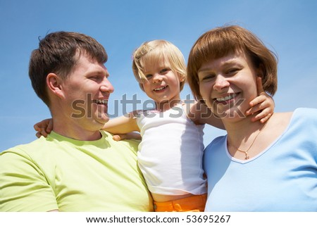 happy family portrait of attractive couple with their young daughter background on the sky