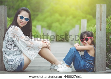 happy family, Portrait of beautiful happy smiling girl is with her mother  outdoor in nature on sunny day - stock photo