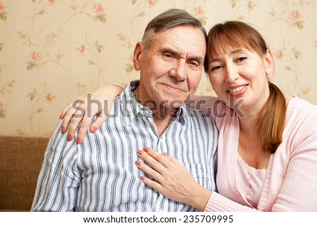 Happy family. Portrait of elderly couple and adult daughter happily looking at camera. Senior man, woman with their caregiver at home. - stock photo