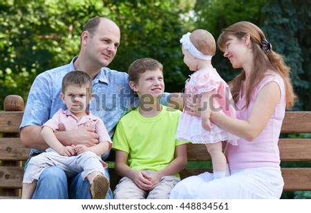 happy family portrait on outdoor, group of five people sit on wooden bench in city park, summer season, child and parent - stock photo