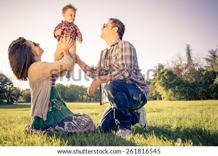 Happy family portrait - Portrait of young beautiful couple with kid having fun in a park - Vintage look - stock photo