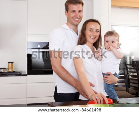 Happy family portrait with mother father and son in kitchen - stock photo