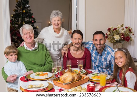 Happy family posing and looking at camera at home in the living room - stock photo