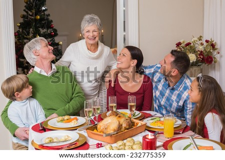 Happy family posing and looking the grandmother at home in the living room - stock photo
