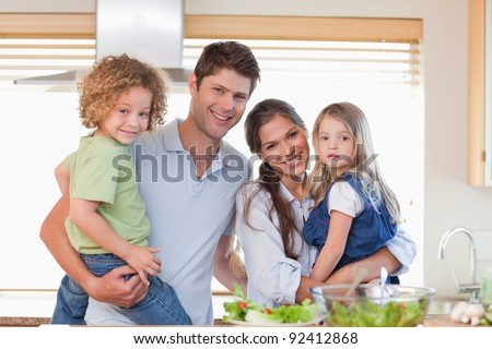 Happy family posing in their kitchen - stock photo