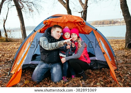 Happy family posing sitting in a tent - stock photo