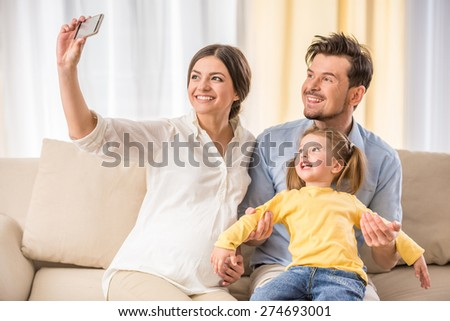 Happy family: pregnant mother, husband and kid girl are making a picture. - stock photo