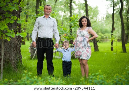 Happy family. Pregnant mother with her husband and son in the park.