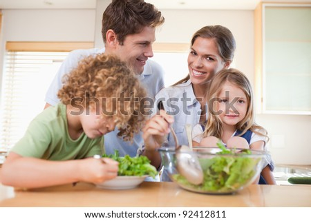 Happy family preparing a salad in their kitchen - stock photo