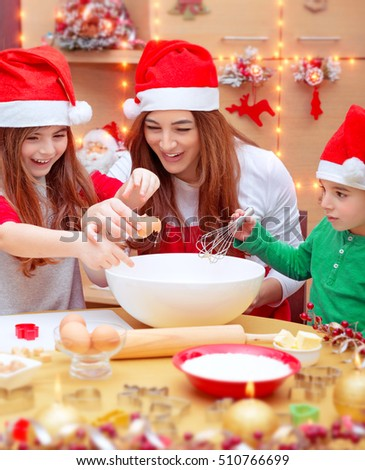 Happy family preparing for Christmas, mother with two cute kids wearing red Santa hat, making a homemade cookies on the decorated kitchen at home, happy winter holidays