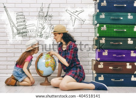 happy family preparing for the journey. mother and daughter looking at a globe and choose a country to travel. - stock photo