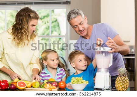 Happy family preparing healthy smoothie in the kitchen - stock photo