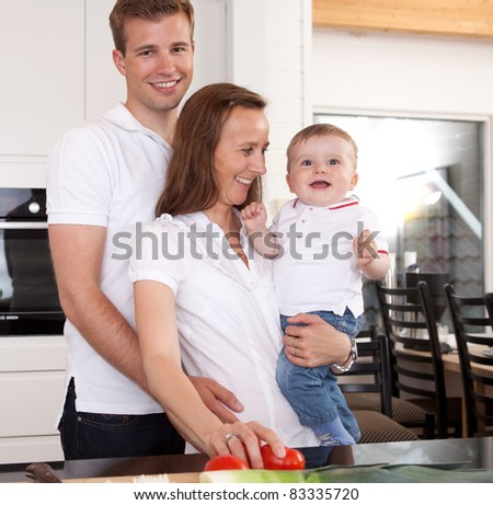 Happy family preparing meal with father giving the mother a hug - stock photo