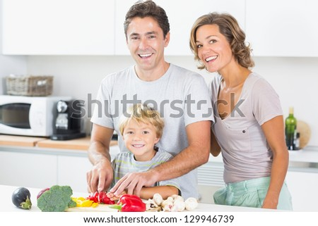 Happy family preparing vegetables together in kitchen - stock photo