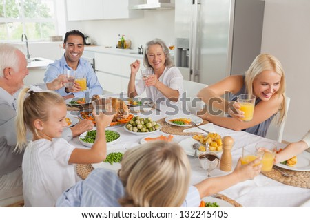 Happy family raising their glasses together in the kitchen - stock photo
