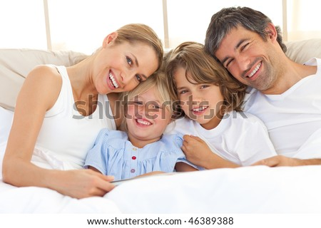 Happy family reading a book  lying in bed - stock photo