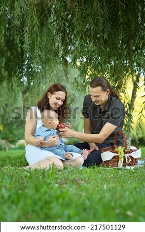 Happy family reading a book to little son at the picnic in the park - stock photo