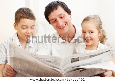 Happy family reading a newspaper. Father with daughter and son - stock photo