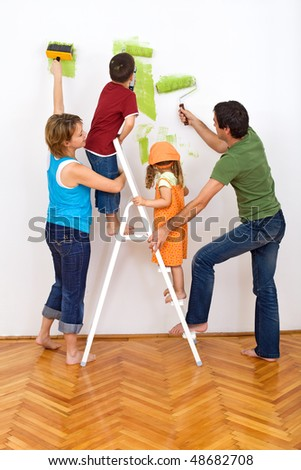 Happy family redecorating the house - painting the wall - stock photo