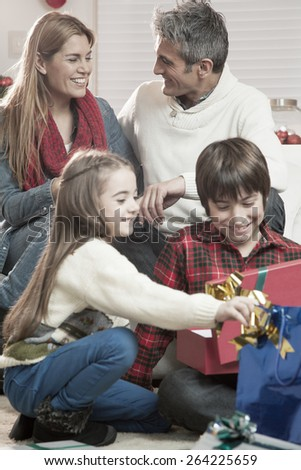 Happy family relaxing at home with Christmas presents. - stock photo