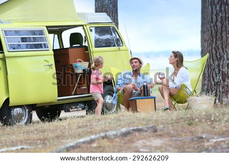 happy family relaxing by camper van in summer - stock photo